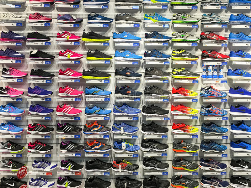Fonctionnement et chaussures de sport à vendre dans l'affichage de magasin de chaussures d'habillement de mode images libres de droits