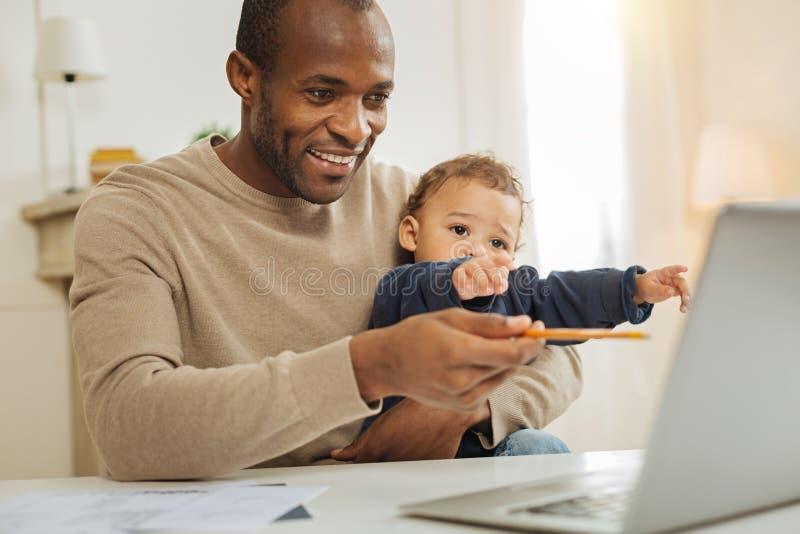 Fonctionnement et garde d'enfants heureux d'homme d'affaires image libre de droits