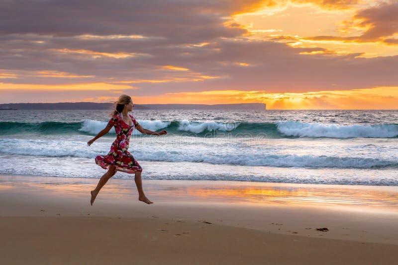 Fonctionnement femelle le long de la plage en sable humide photo libre de droits
