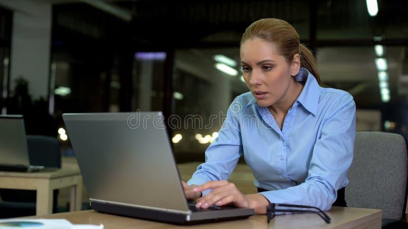 Fonctionnement femelle nerveux sur l'ordinateur portable la nuit, le travail stressant posant des problèmes de santé photos stock