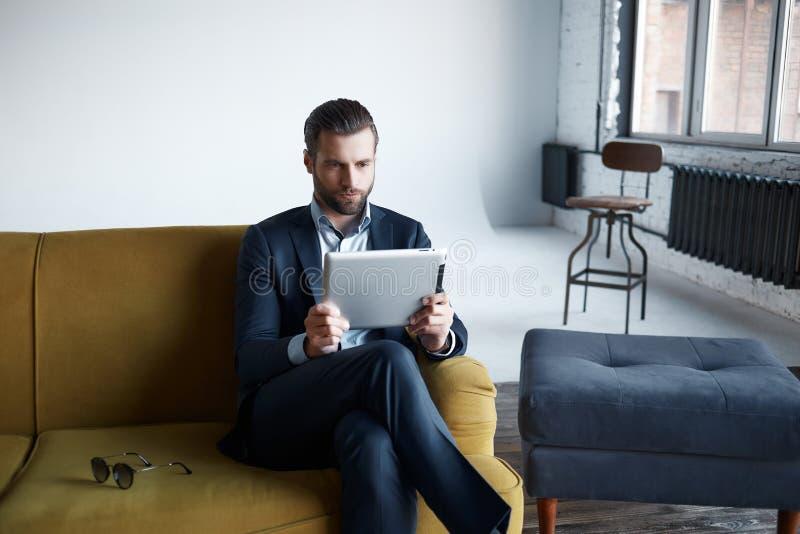 fonctionnement L'homme d'affaires réussi et à la mode utilise un comprimé tout en se reposant sur le sofa au bureau moderne photos libres de droits