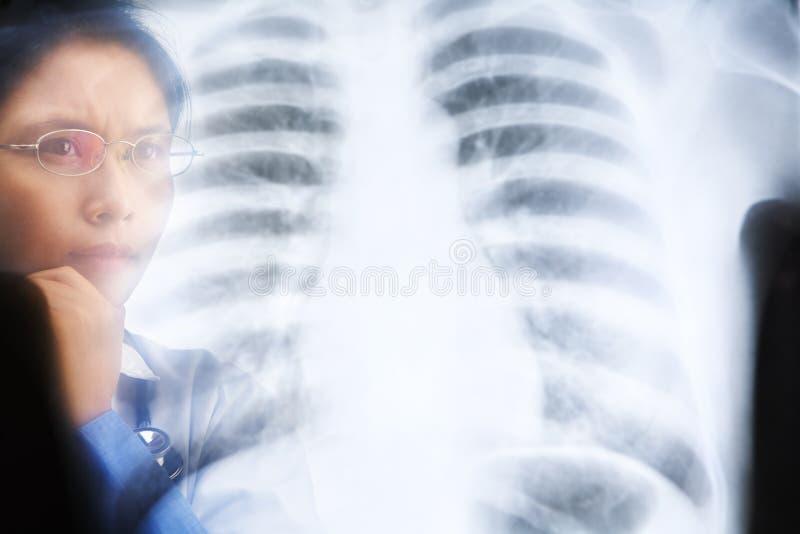 Fonctionnement occupé de docteur féminin asiatique sur le résultat de rayon X image stock