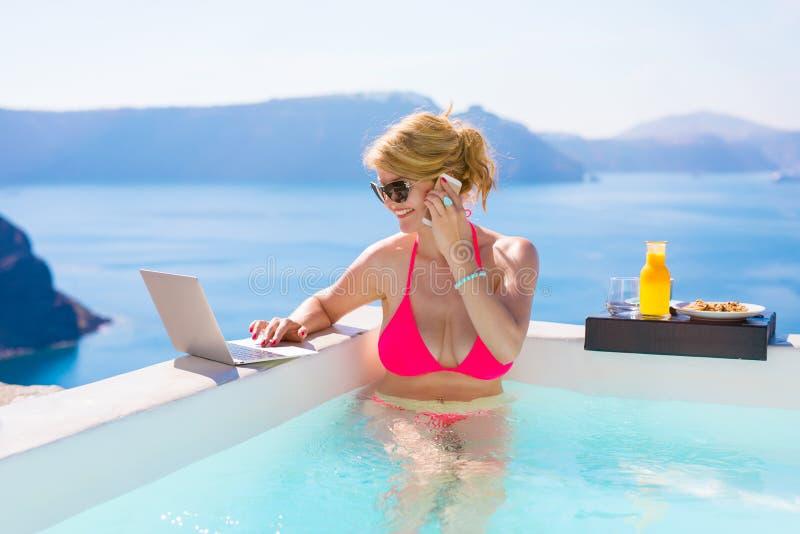 Fonctionnement occupé de femme d'affaires tandis que des vacances dans la piscine image stock