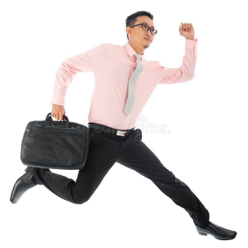 Fonctionnement ou sauter asiatique d'homme d'affaires images stock