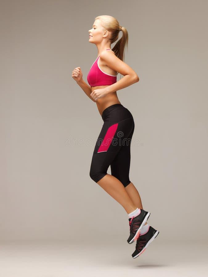 Fonctionnement ou sauter sportif de femme images stock