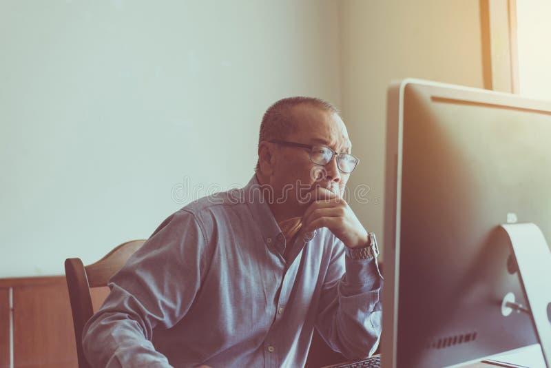 Fonctionnement sérieux asiatique d'homme supérieur et d'utilisation ordinateur à la maison pendant le matin photos stock