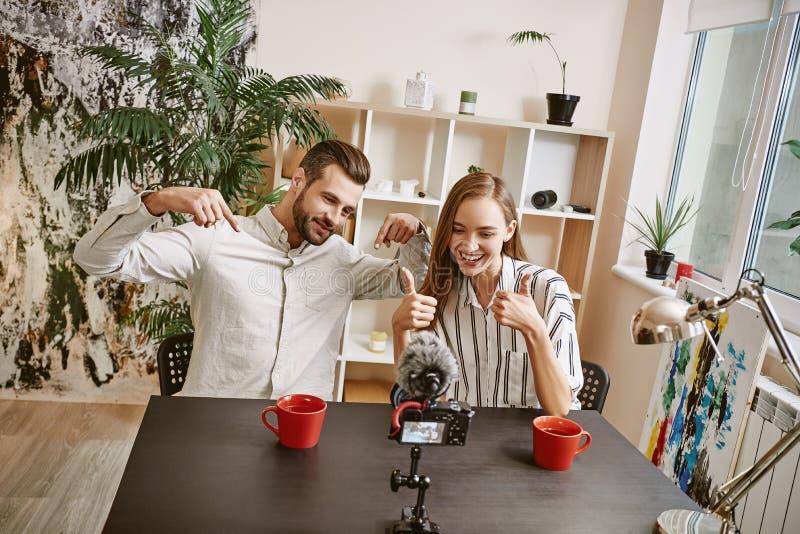 Fonctionner ensemble Le mâle positif et les bloggers féminins font le nouveau contenu visuel pour leur blog populaire image libre de droits