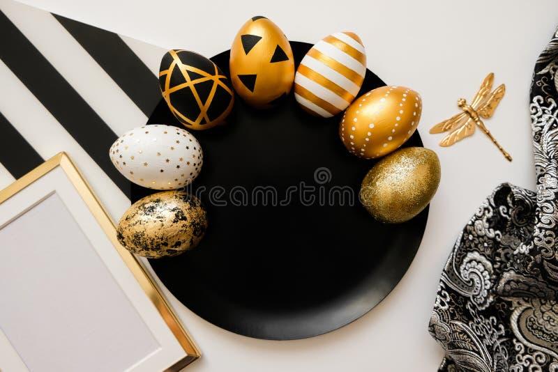 Fond élégant avec la décoration Composition avec les oeufs décorés d'or de Pâques du plat noir Concept à la mode de Pâques de con photo stock