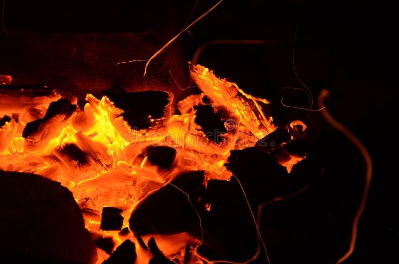 Fond abstrait, charbons brûlants, feu et étincelles sur un fond noir images stock