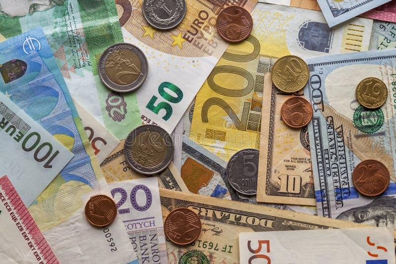 Fond abstrait coloré fait en différentes pièces en métal, billets américains et ukrainiens et euro devise de billets de banque Ar image stock