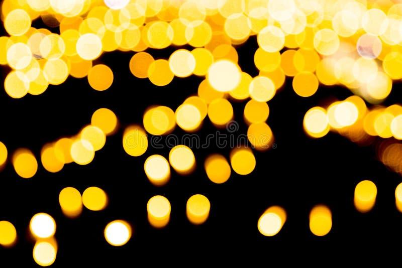 Fond abstrait de f?te d'or avec le bokeh defocused et brouill? beaucoup autour de la lumi?re jaune sur le fond d'obscurit? de No? image libre de droits