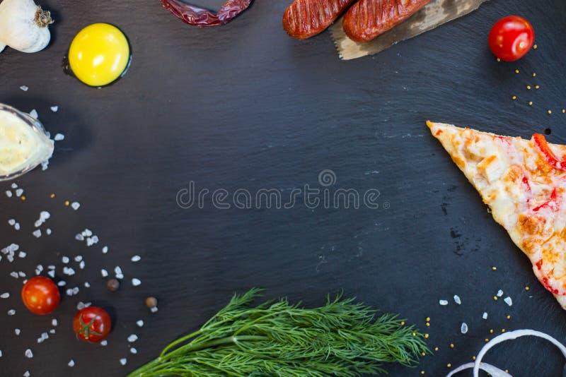 Fond Ardoise noire avec la pizza, les légumes, l'épice de nourriture et les herbes photographie stock