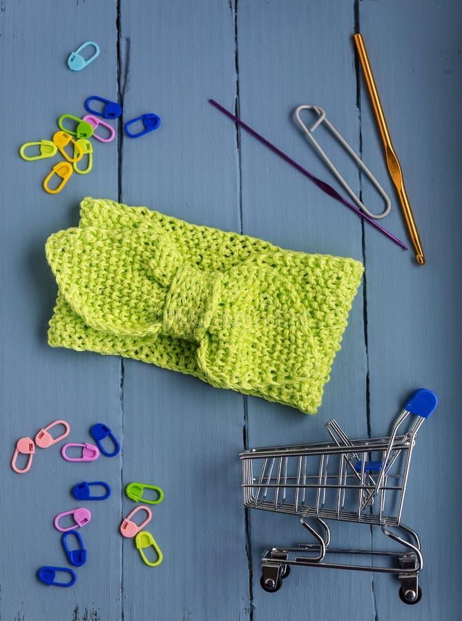Fond arrière pour des couturières, bandeau tricoté vert pour des filles, boules, crochets sur un fond en bois bleu photographie stock libre de droits
