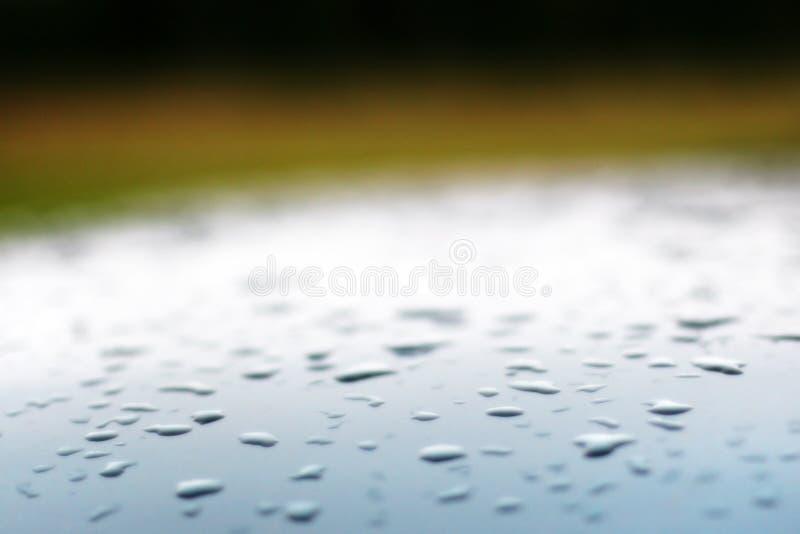 Fond avec des baisses brouillées sur le toit d'une voiture bleue argentée et d'un contexte vert photos stock