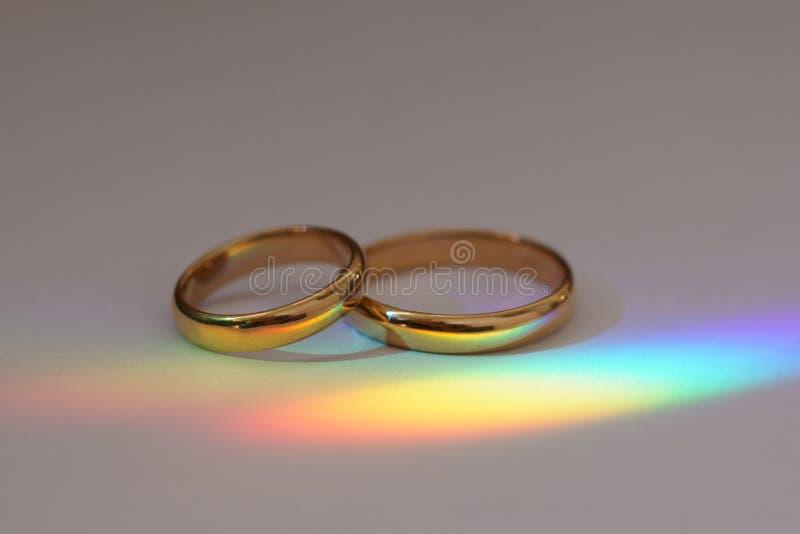 Fond avec deux anneaux de mariage avec l'arc-en-ciel photos stock
