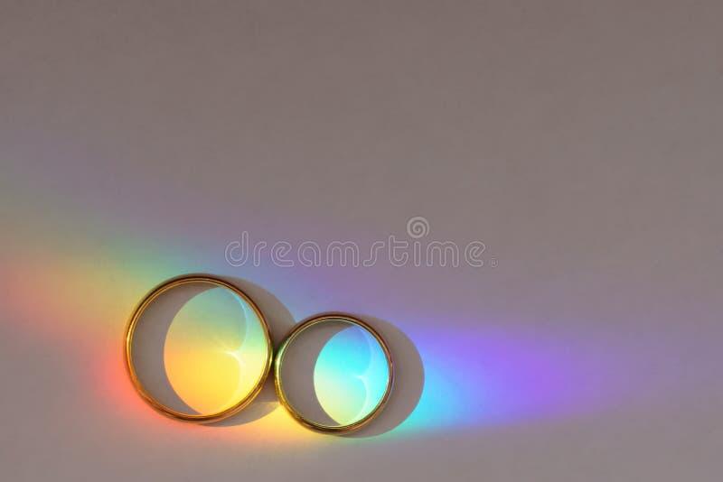 Fond avec deux anneaux de mariage avec l'arc-en-ciel photo libre de droits