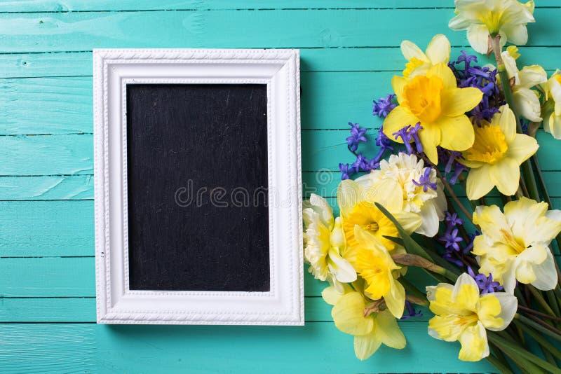 Fond avec les fleurs colorées lumineuses de ressort et le tableau noir vide photos stock