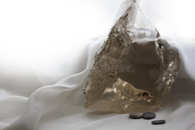 Fond avec un grand cristal de quartz transparent et quelques petites pierres photographie stock