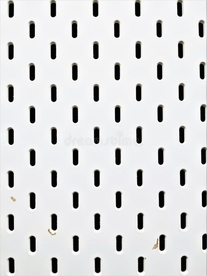Fond blanc avec de petits trous Il sert de séparation à la disposition du lieu de travail de bureau photographie stock