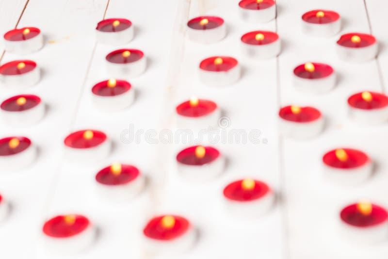 Fond blanc brouillé avec les bougies brûlantes rouges images stock