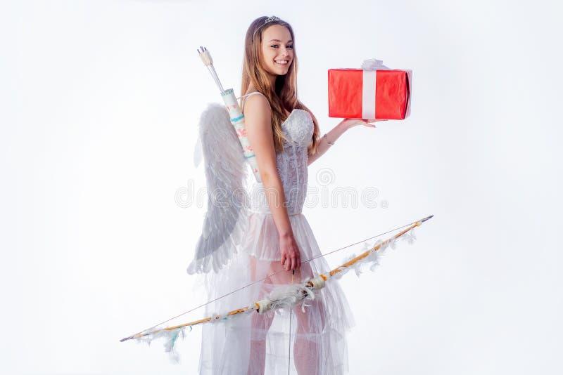 Fond blanc d'isolement Cupidon dans le Saint Valentin Fille habillée comme ange sur un fond clair Portrait d'un cupidon images stock