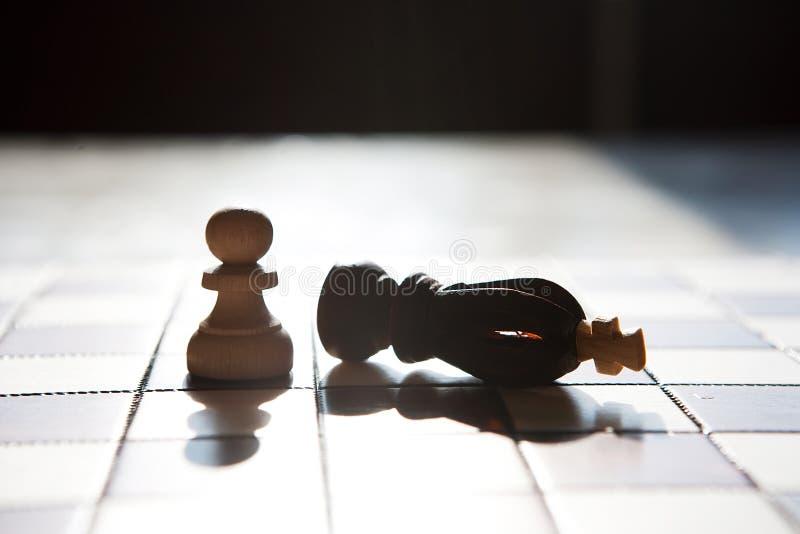 Fond blanc de roi d'échecs de noir de battement de gage à bord image stock