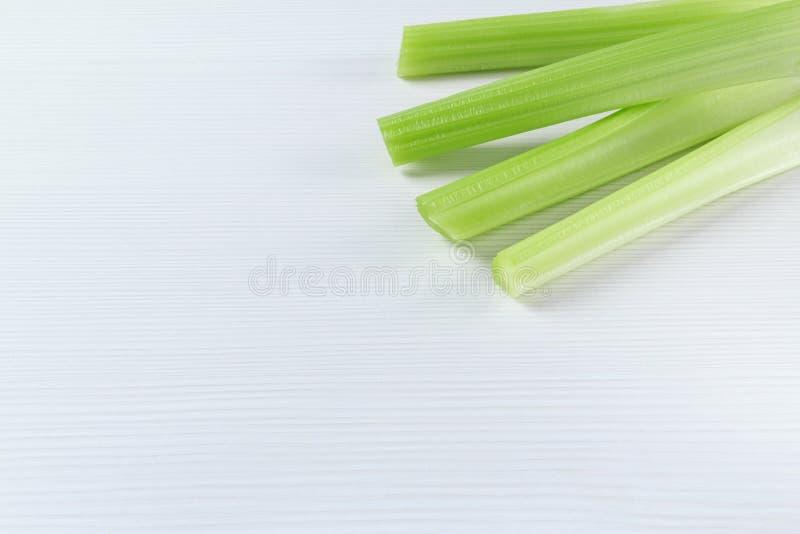 Fond blanc et vert latéral faisant le coin avec le céleri vert cru images stock