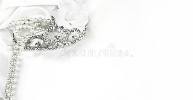 Fond blanc mou de jeune mariée de décorations nuptiales de mariage, couronne argentée et perles sur le satin avec l'espace pour l photo stock