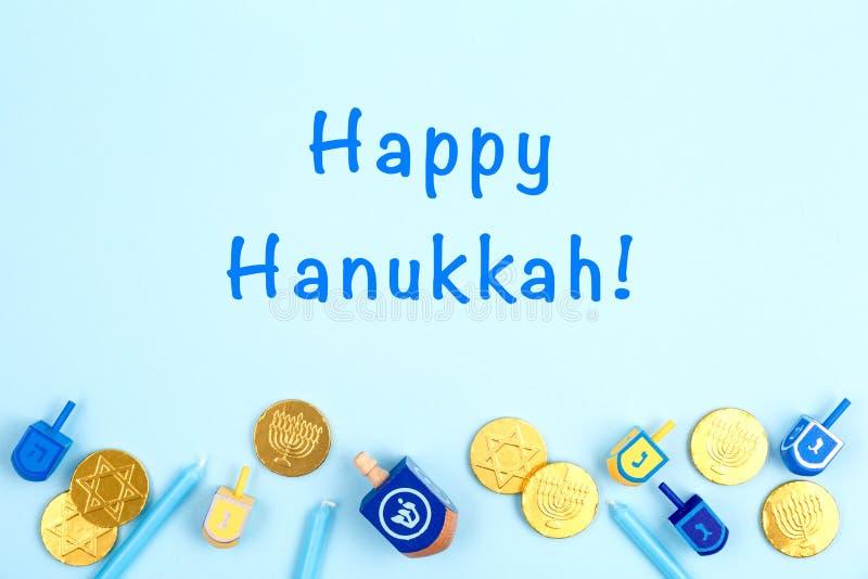 Fond bleu avec des rêves multicolores, des bougies menora et des pièces de chocolat et une formule Happy Hanukkah Hanoukka et image libre de droits