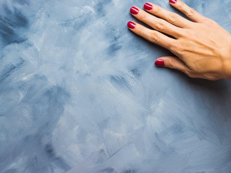 Fond bleu de couleur en pastel avec la main du ` s de femme photographie stock