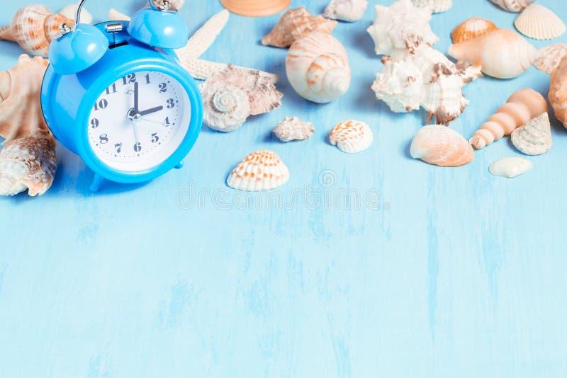 Fond bleu de mer avec des réveils et des coquillages, des vacances d'été et concept de temps de vacances photos libres de droits