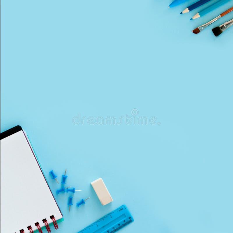 Fond bleu et fournitures scolaires bleues De nouveau à l'école l plat photographie stock libre de droits
