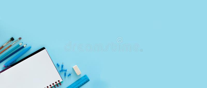 Fond bleu et fournitures scolaires bleues De nouveau à l'école l plat photos stock