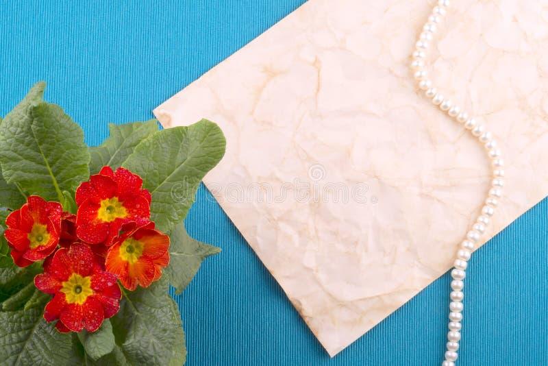 Fond bleu, vieux papier, ficelle des perles, fleurs rouges Postc image libre de droits