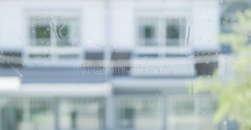 Fond brouillé abstrait d'éclaboussure de pluie sur la fenêtre avec le fond à la maison image libre de droits