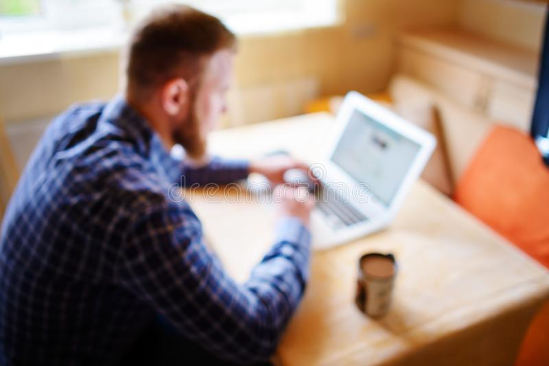 Fond brouillé, homme d'affaires à l'aide de l'ordinateur portable sur le lieu de travail - vue arrière image stock