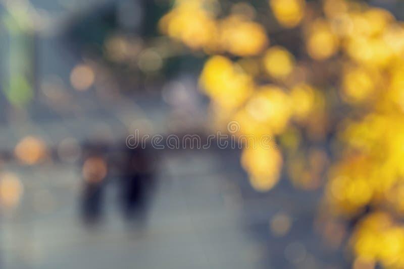 Fond brouill? d'automne Feuilles lumineuses et personnes defocused jaunes d'arbre marchant dans la rue image libre de droits