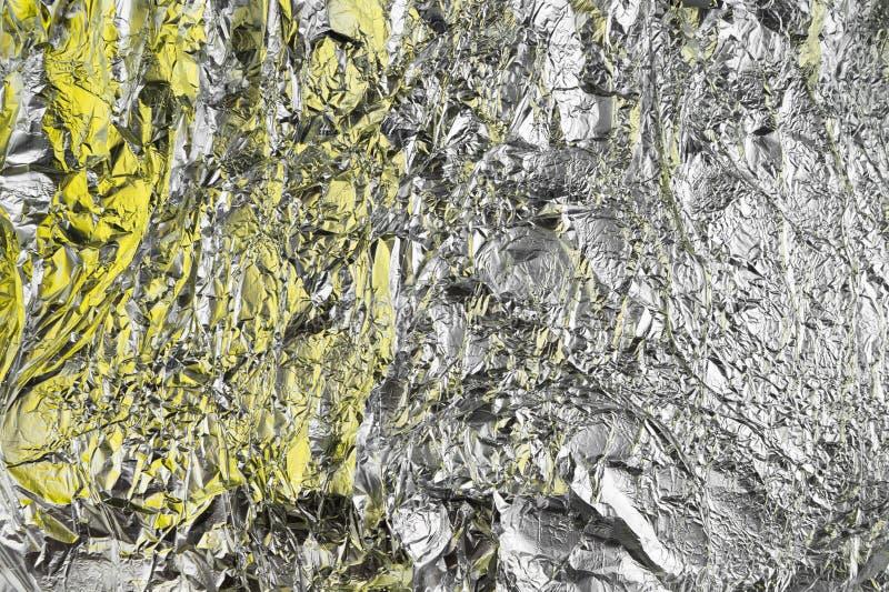 Fond chiffonné abstrait d'aluminium Fond grunge de photo Ombres jaunes photographie stock