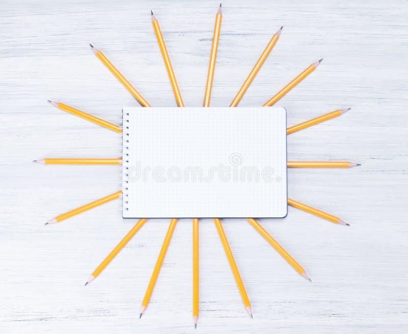 fond clair des crayons simples, carnet ci-dessus, le soleil jaune photos libres de droits