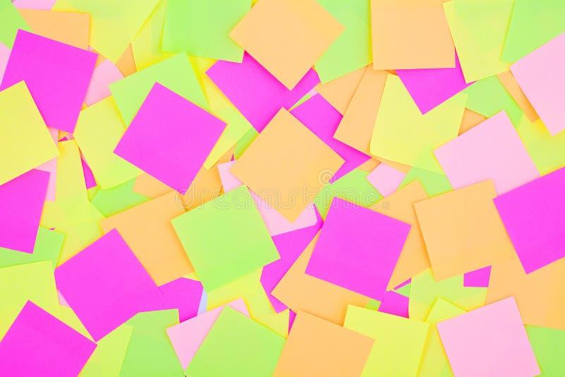 Fond coloré de beaucoup de notes de post-it Le rappel coloré rayonnant note le papier peint Papier multicolore de post-it image stock