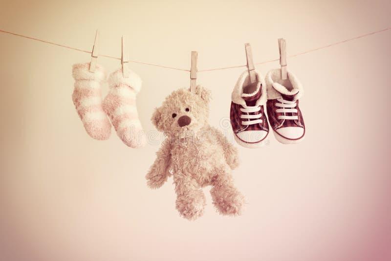 Fond coloré pour le bébé avec deux chaussettes, espadrilles et ours de nounours roses avec l'espace de copie photo stock