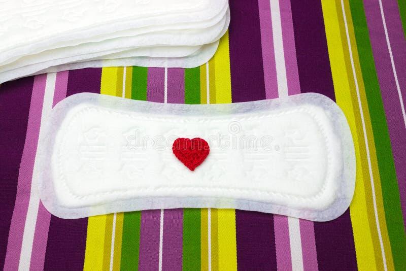 Fond coloré rayé lumineux avec la protection quotidienne sanitaire de règles propres blanches, coeur de crochet Prot tendre mou d photos stock
