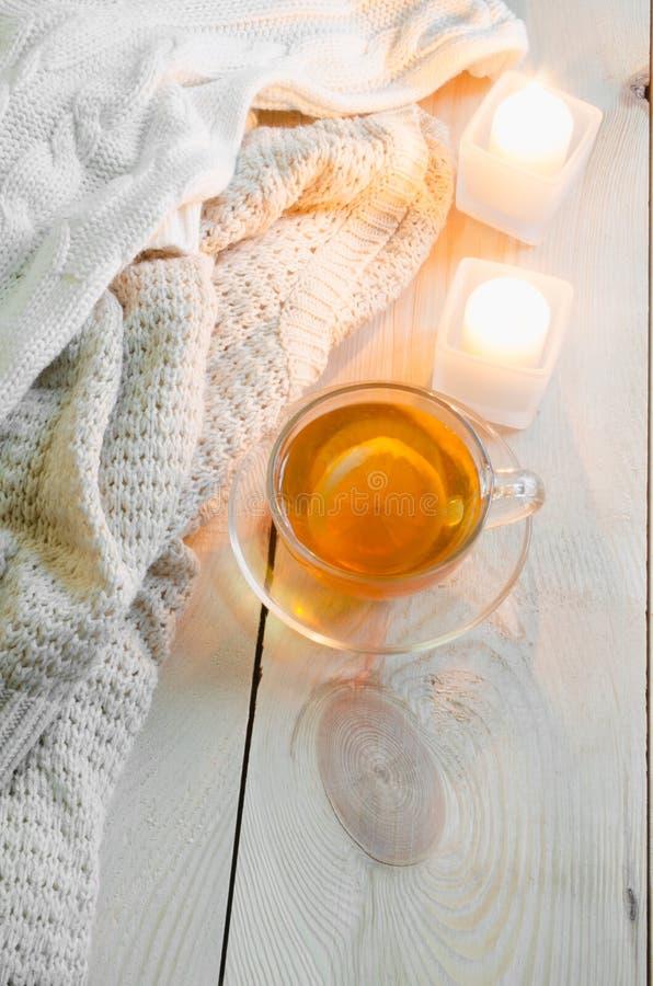 Fond confortable et mou d'hiver Chandails ou couvertures chauds, bougies, tasse de thé photographie stock libre de droits