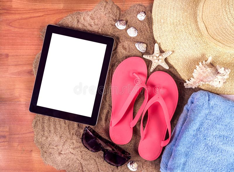 Fond d'été avec les bascules électroniques, la serviette, les étoiles de mer et les verres avec la tablette numérique avec l'écra photos libres de droits