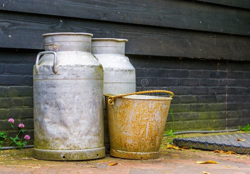 Fond d'agriculture, équipement de ferme de cru, boîtes de lait en métal et un vieux seau rouillé photo libre de droits