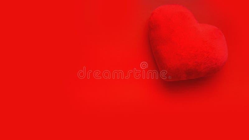 Fond d'amour de jour de valentines avec le coeur mou de jouet sur le fond rouge images stock