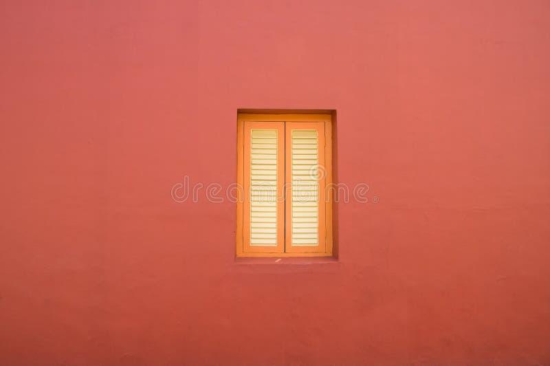 Fond d'architecture de Minimalistic de fenêtre orange sur le mur rouge de plâtre image libre de droits