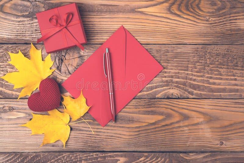 Fond d'automne avec des feuilles d'érable, enveloppe rouge, stylo, boîte-cadeau, coeur tricoté sur les conseils en bois Copiez l' image libre de droits