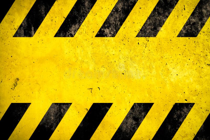 Fond d'avertissement avec les rayures jaunes et noires peintes au-dessus de la texture jaune de façade de mur en béton et de l'es images stock