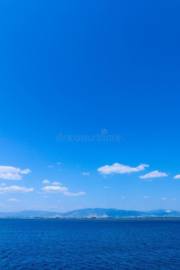 Fond d'eau de mer, montagnes brumeuses, contexte Calme bleu d'océan image stock